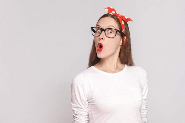 주근깨, 검은 안경, 빨간 입술, 머리띠가 있는 흰색 티셔츠를 입은 아름답고 감정적인 젊은 여성의 믿을 수 없는 초상화입니다. 밝은 회색 배경에 격리된 실내 스튜디오 촬영.