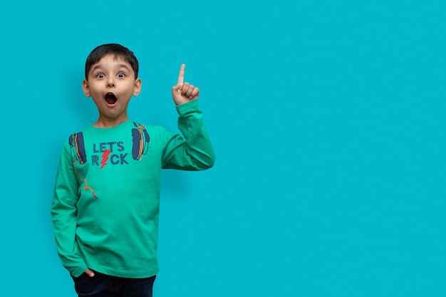 うわー見て、ここに宣伝してください!背景の空の場所を指している驚いたかわいい男の子の肖像画、コピースペースを示している驚いた男子生徒