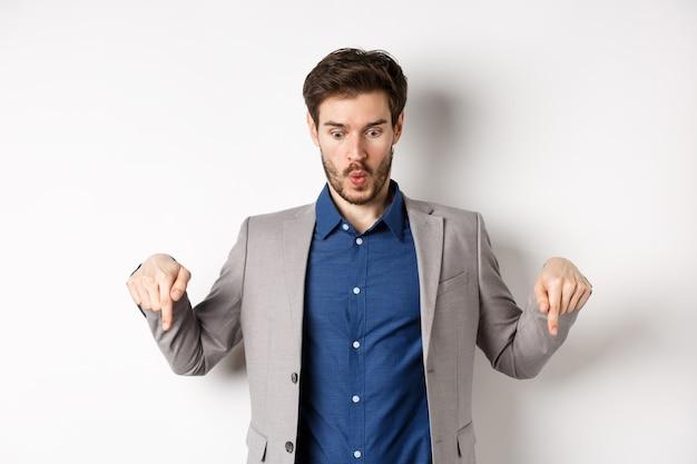 Ух ты посмотри на это. впечатлен и взволнован бизнесмен в костюме, указывая пальцами вниз, глядя на нижнюю рекламу с удивленным лицом, стоя на белом фоне.
