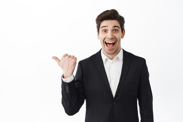 Wow look there. excited male entrepreneur, estate agent in suit pointing finger left and smiling amazed, showing awesome price or discount, standing over white wall