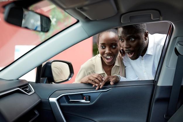 うわー、見て、若いアフリカのカップルが自動車に興味を持っているシックな車