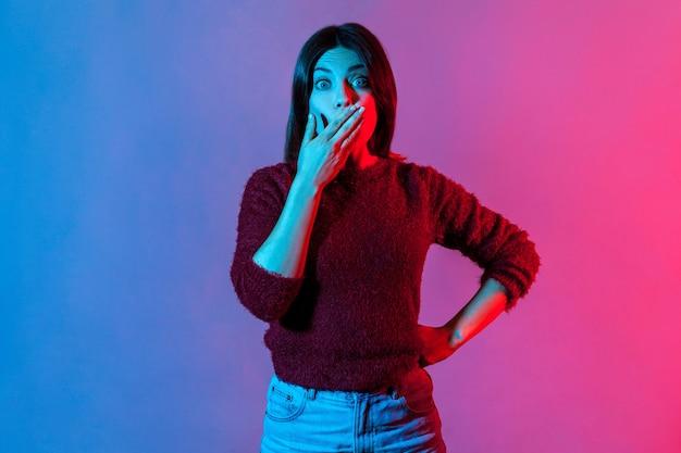 わお!手で口を覆い、大きな目で見ている驚いた女性のネオンの光の肖像画