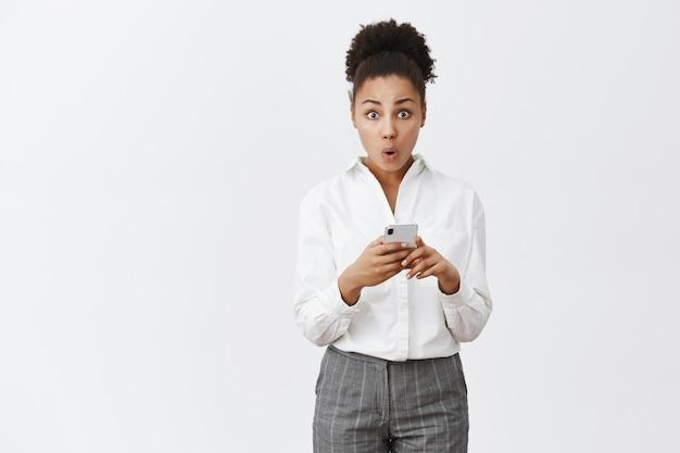 업데이트 후 와우 새로운 기능. 우아한 흰색 셔츠와 바지에 호기심이 귀여운 아프리카 계 미국인 여자의 초상화, smarpthone을 들고 접힌 입술과 놀란 표정으로 감동