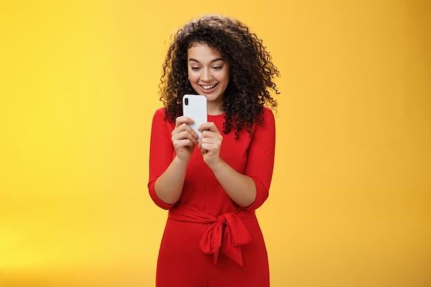 すごい新しい携帯電話。黄色い壁の上でクールなアプリやゲームをプレイしているように面白がって画面を見ているスマートフォンを保持している赤いドレスを着た印象的で驚いた格好良い縮れ毛の女性。