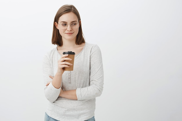 Wow nice butt. portrait of naugty good-looking enthusiastic woman with brown hair in glasses smirking and gazing at lower right corner drinking coffee while standing near cafe posing over gray wall