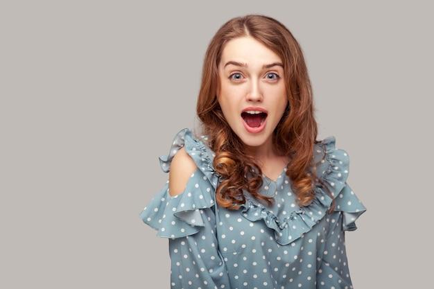 うわー、なんてことだ!驚いて、口を開けてカメラを見て驚いたブルネットの女の子のフリルブラウス
