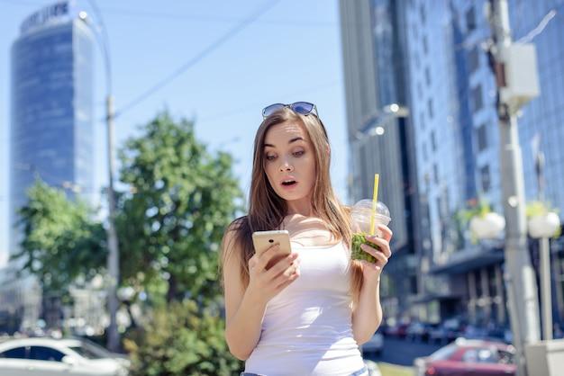 うわーomgポジティブファンキーな人々のモデルのコンセプト。電話スクリーンの口を開けてカジュアルな服装を見つめている冗談コミック顔をゆがめた女性の写真の肖像画を閉じる