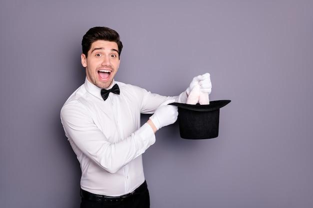 Ого, кролик в цилиндрической шляпе! возбужденный сумасшедший смешной волшебник держит кепку, чтобы развлечь публику цирка в белой рубашке с черным бантом, изолированной над серой стеной Premium Фотографии