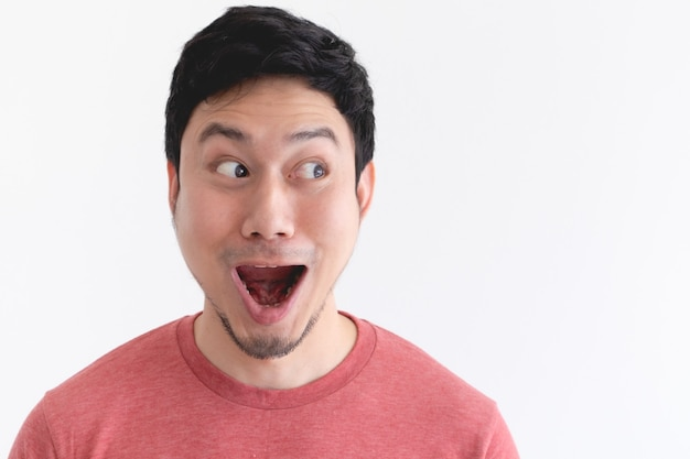 Wow and shocked face of funny asian man isolated on white wall