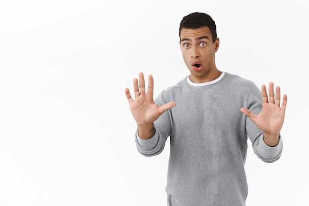 Wow slow down, wait sec. overwhelmed and panicking hispanic guy raising hands in stop gesture