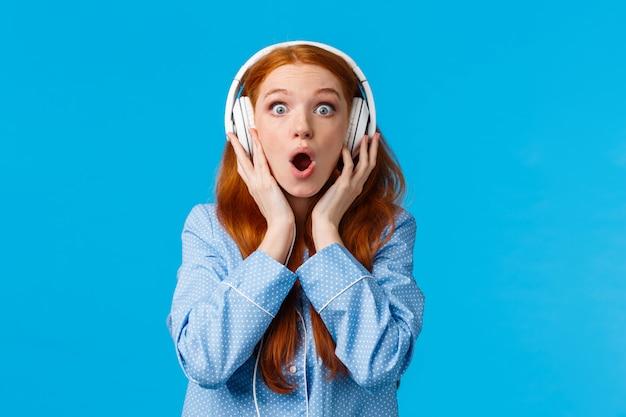 Ух ты такой чистый звук. удивленная и восторженная симпатичная рыжеволосая женщина в пижаме, задыхаясь, слышит потрясающую музыку в наушниках, носит большие наушники, голубая стена