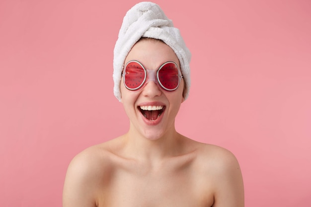 うわー!とてもクール!目の上にスパマスクを置き、頭にタオルを置き、口と目を大きく開いた後の若い幸せな驚きの女性は、クールなニュースを聞いて立っています。
