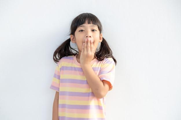 わお。眉を上げて開いた口を手で覆っている感情的な愛らしいアジアの少女のスタジオショットは驚きとショックを受け、予期しないニュースに本当に驚いた反応を示しています