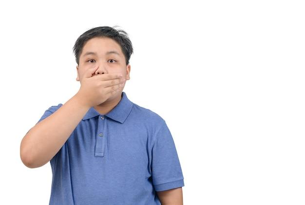 わお。眉を上げ、開いた口を手で覆って驚いてショックを受けた感情的な肥満の少年のスタジオショット、