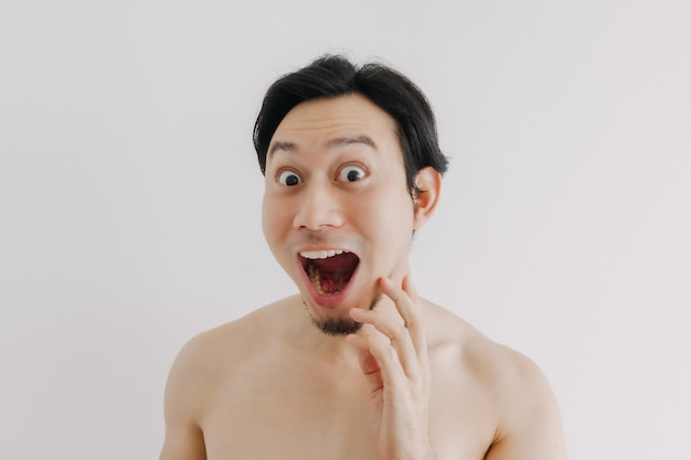 Wow and surprise face of man using skin care product on his face