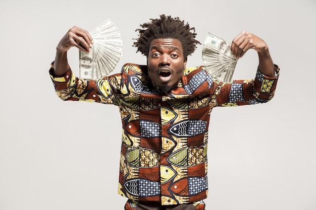 우와! 많은 달러를 들고 놀란 아프리카 사업가가 너무 행복합니다. 실내, 회색 배경에 고립