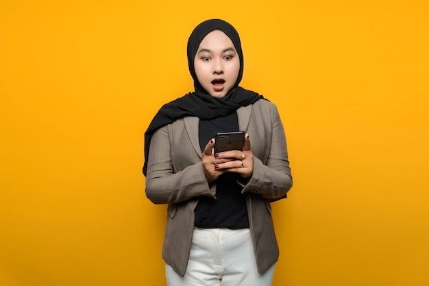 Wow and surprised face of asian woman holding smartphone