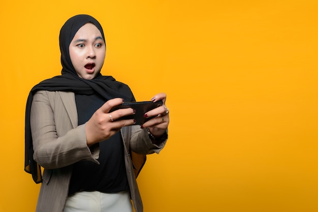 Wow and surprised face of asian woman play smartphone