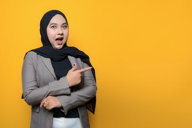 Wow and surprised face of asian woman pointing to empty space