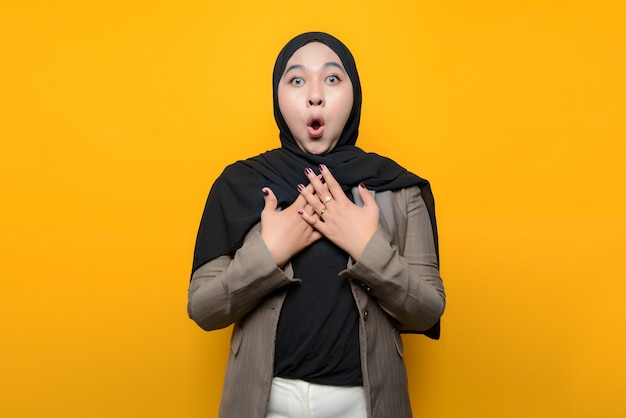 Wow and surprised face of asian woman on yellow