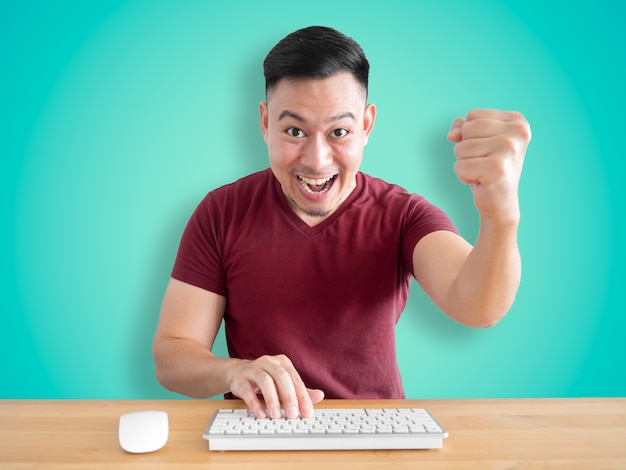 Wow and surprised face of cheerful asian man sitting in front of his computer in his office.