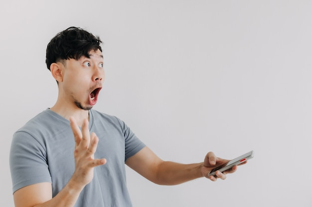 Wow and surprised face of man hold a smartphone isolated on white wall