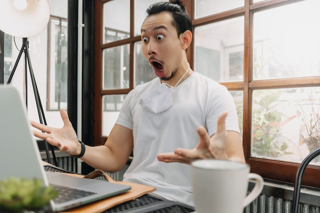 Wow and surprised face of man work with his laptop and successful