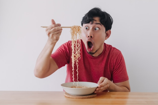 Wow and surprised funny face of man eat instant noodle