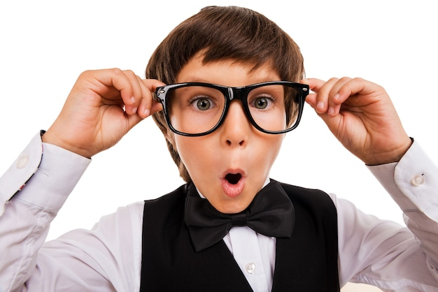 Wow! surprised little boy keeping mouth open and adjusting his glasses while standing isolated on white