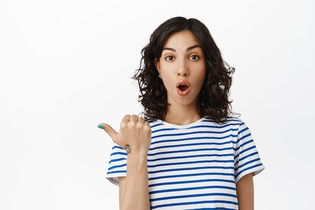 Wow take look. excited brunette woman with pierced nose, pointing left, gasp and stare amazed, checking out advertisement, recommend store, standing  on white