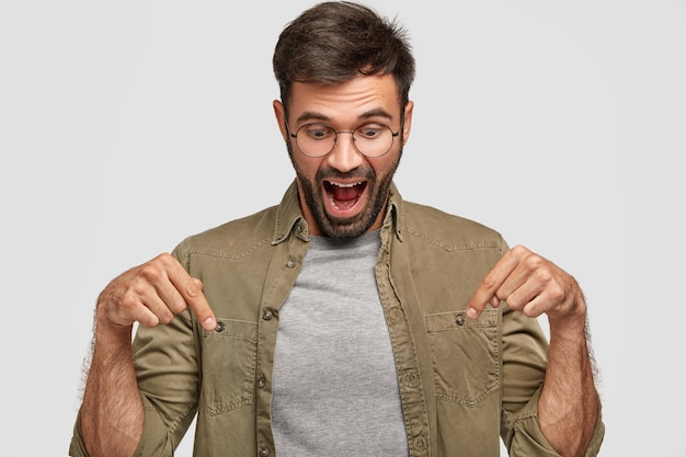 Wow, that`s amazing! amazed shocked young male looks with surprisement down, points with both index fingers, dressed casually, opens mouth widely in astonishment, isolated over white wall