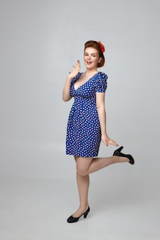 ワオ。表情を盛り上げ、口を覆い、片足を持ち上げる60年代のレトロな衣装を着た魅力的なファッショナブルな女性モデルの縦の写真。軽薄なピンナップガールのポーズ
