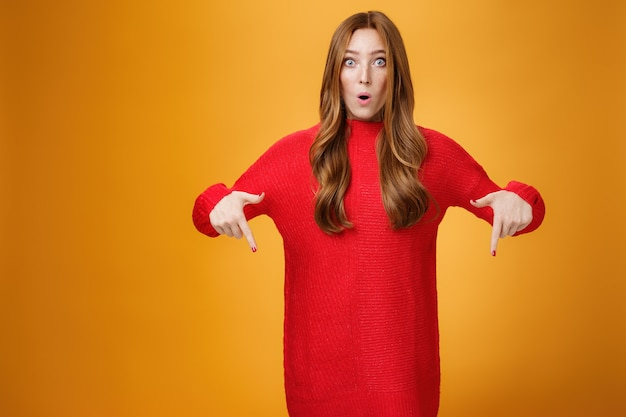 Ух, какая классная акция. портрет впечатленной и удивленной милой удивленной рыжей женщины в стильном теплом вязаном платье, изумленно складывая губы, указывая вниз и смотрящий в камеру