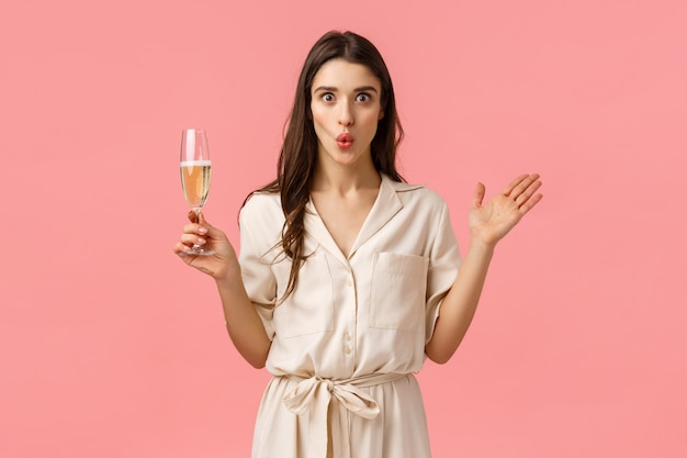 Wow wonderful news lets celebrate. surprised and amused attractive brunette woman in dress, having fun partying, raising hands amazed, folding lips excited and holding glass champagne
