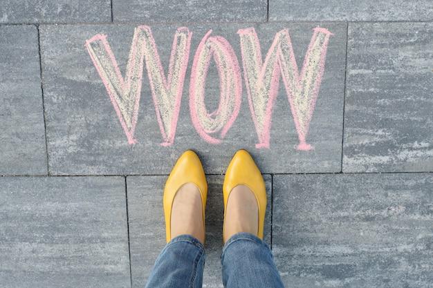 Wow written on gray sidewalk with woman legs in feet in yellow shoes