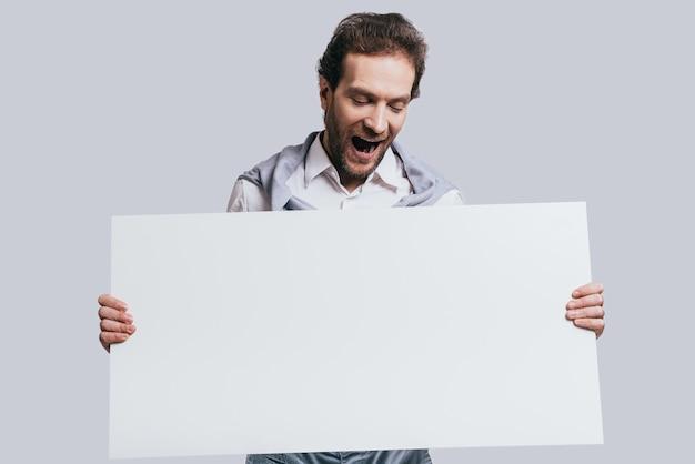 わお!立っている間驚いた顔で空白のフリップチャートを保持しているスマートカジュアルな服を着た若い自信のある男