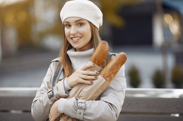 Wowan in a white beret  in a city with a baguette