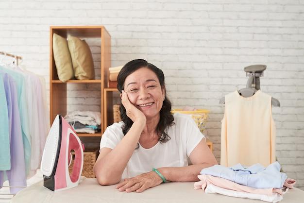 アイロン台に寄りかかって元気に笑顔で家事を楽しんでいるアジアのシニアwowanの中間のクローズアップ