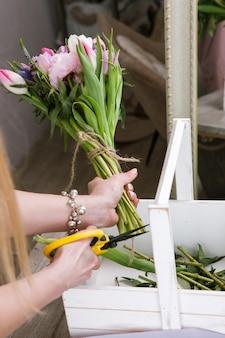 Wowoman 튤립 꽃다발 평면도 만들기. 인식 할 수없는 꽃집은 봄 결혼식 플로리스트가 나무 배경에 워크샵에서 조립합니다.