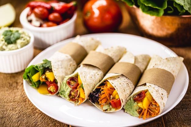 卵、有機野菜、アボカドクリームを含まない生地で作ったラップまたはビーガンブリトー。健康的な簡単な食事。