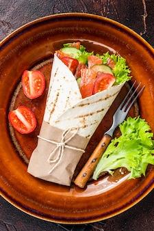 Сэндвич с рулетом в обертке с рыбой, лососем и овощами. темный фон. вид сверху.