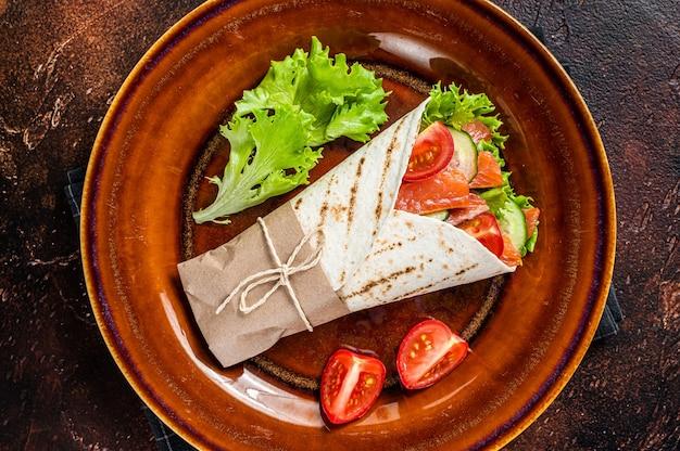 Сэндвич в рулетах с рыбой, лососем и овощами. темный стол. вид сверху.