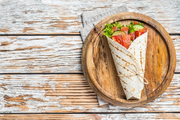 연어 샌드위치를 싸고 생선과 야채로 굴립니다. 흰색 나무 테이블. 평면도.