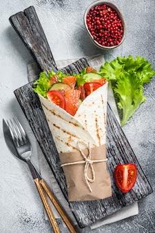 샌드위치를 싸고 생선 연어와 야채로 굴립니다. 화이트 테이블. 평면도.