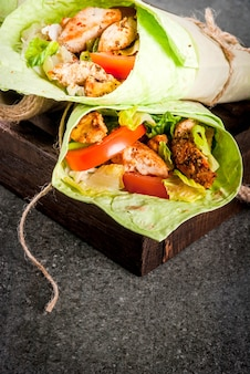 Wrap sandwich with green lavash tortillas with chicken, vegetables and yoghurt sauce