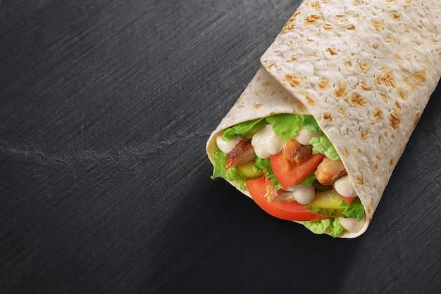 サンドイッチをサラダ、チキン、ソース、トマト、ピクルスで包みます