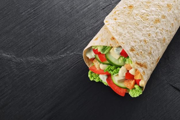 サンドイッチをサラダ、チキン、ソース、トマト、ピクルスで包みます Premium写真