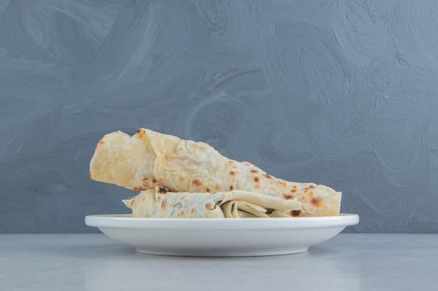 Avvolgere farcito con verdure sul piatto bianco.