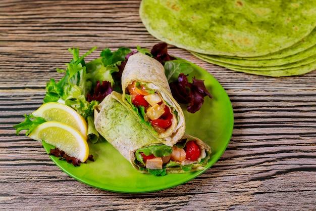 Оберните с жареной курицей и овощами на тарелку с зеленым салатом и лимоном.