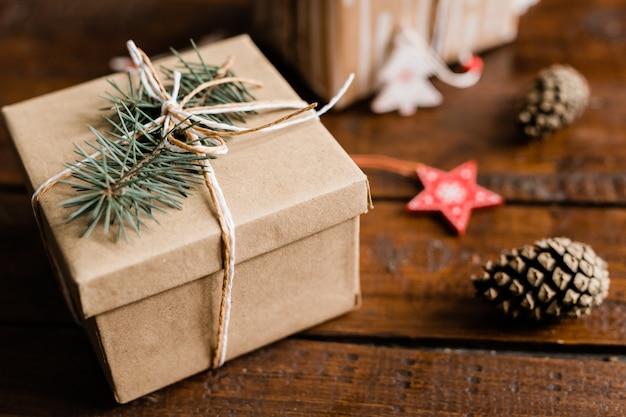 Упакованная подарочная коробка с хвойными деревьями сверху и сосновыми шишками и рождественскими украшениями рядом на деревянном столе